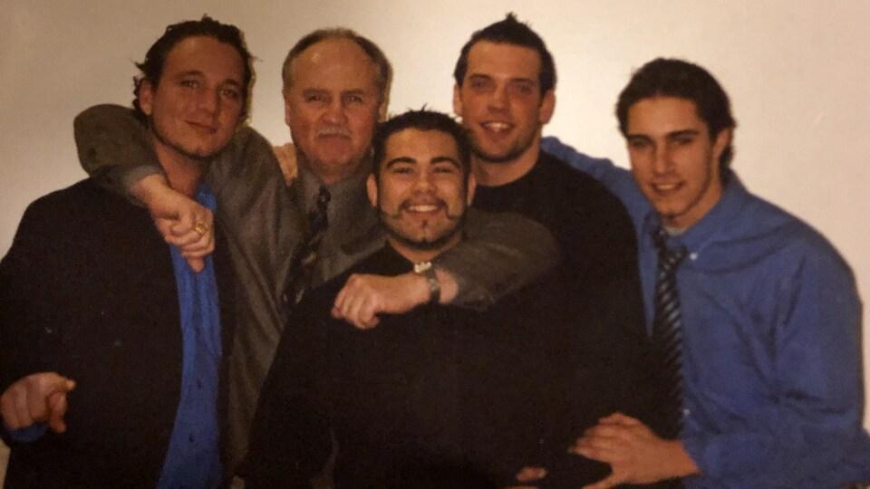 Les quatre hockeyeurs québécois posent en compagnie de leur entraîneur-chef de l'époque, Bob Beatty.