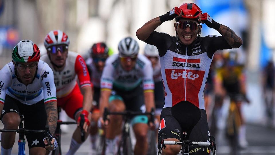 Le cycliste pose les mains sur son casque et sourit en franchissant l'arrivée.