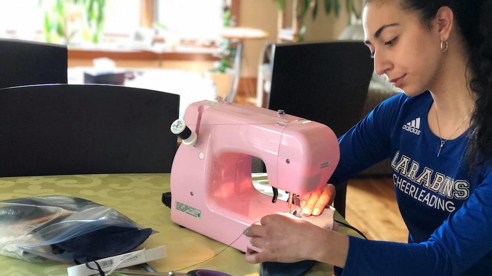 Une jeune femme vêtue d'un chandail bleu confectionne un masque de protection avec une machine à coudre rose.