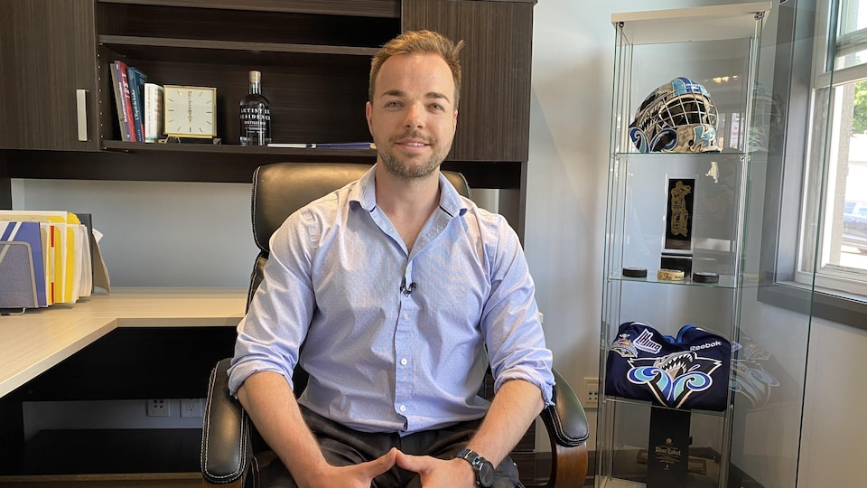 Carl Hozjan pose dans son bureau. Près de lui, des souvenirs datant de son parcours de gardien de but dans la LHJMQ.