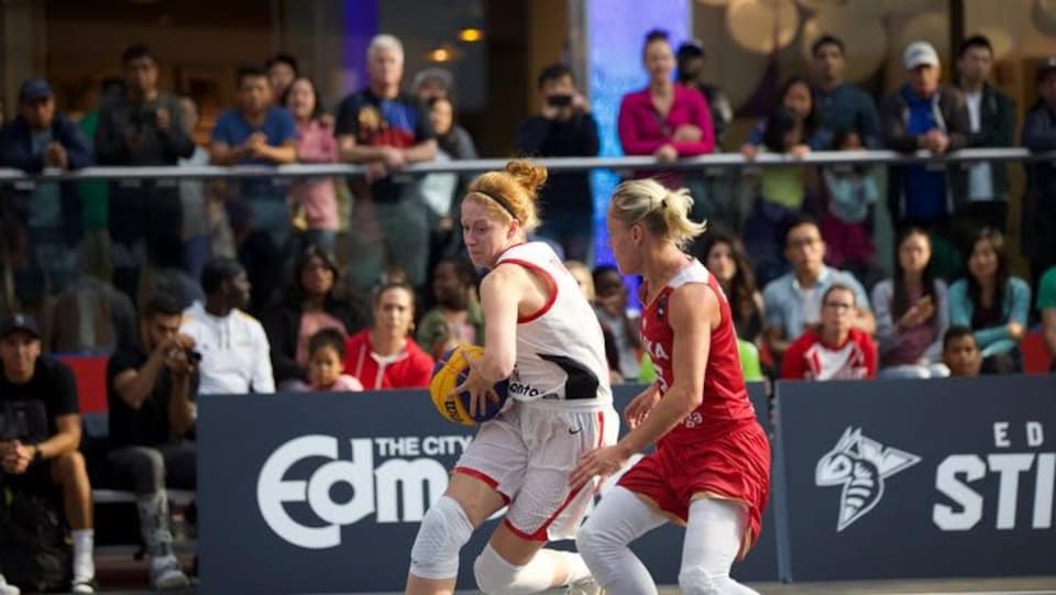 Une joueuse de basketball protège son ballon contre une adversaire
