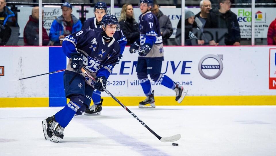 Un joueur de hockey manie la rondelle pendant l'échauffement de son équipe