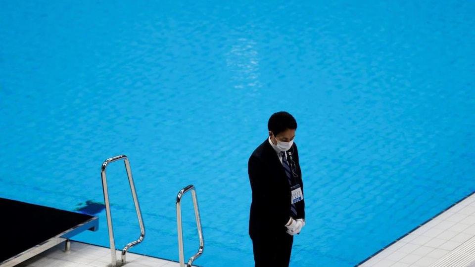 Un officiel masqué se tient devant une piscine vide