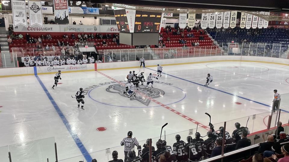Des joueurs de hockey s'affrontent sur la glace. On voit des gradins avec quelques spectateurs et de nombreuses bannière accrochées au plafond.