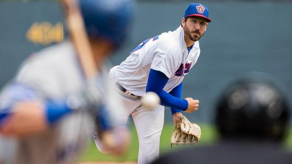 Un lanceur de baseball regarde sa balle arriver au frappeur pendant un match