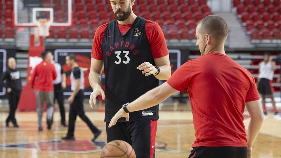 L'entraîneur dribble le ballon que Gasol attend de recevoir.