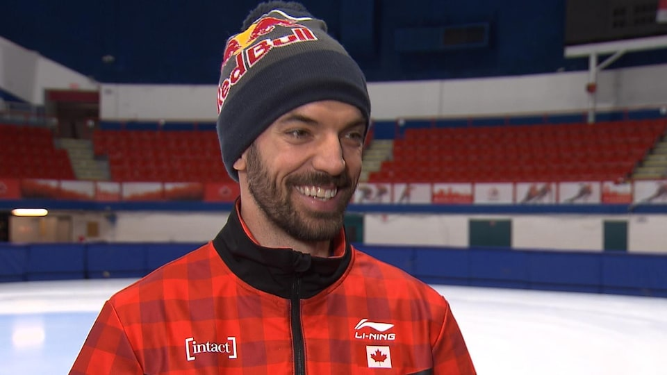 Il sourit sur le bord de la patinoire.