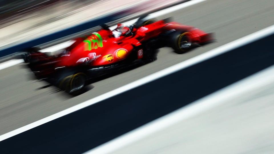 Charles Leclerc roule dans la ligne des puits dans sa Ferrari rouge.