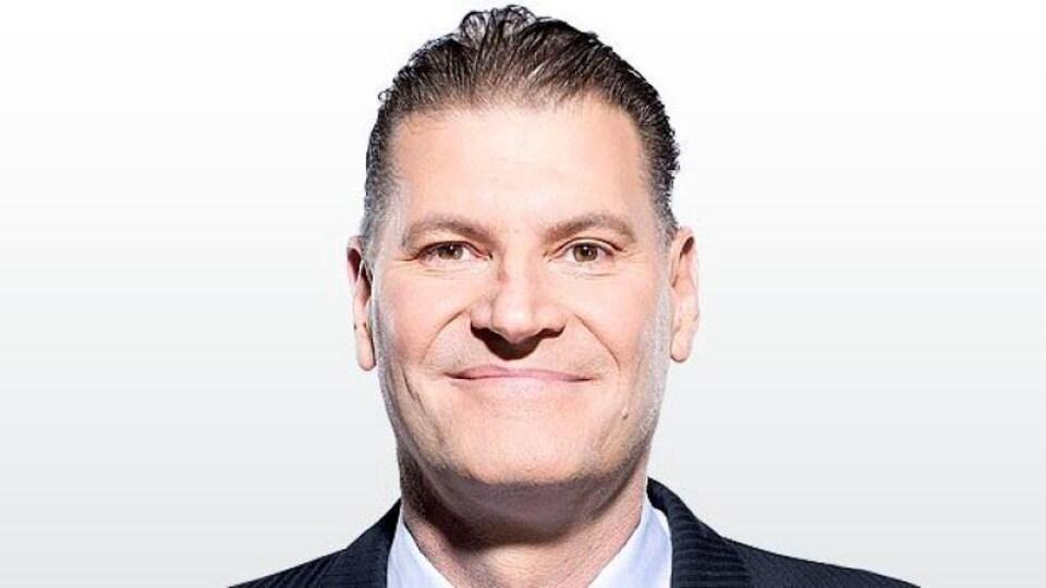 Un homme souriant sur fond blanc