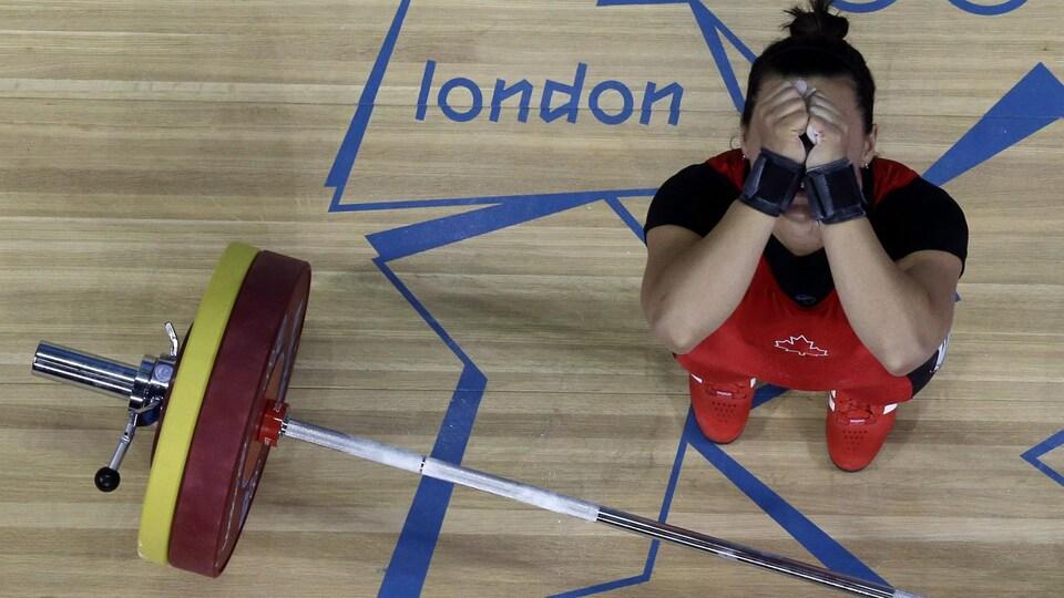 Christine Girard cache son visage avec ses mains après avoir tenté en vain de soulever la barre.