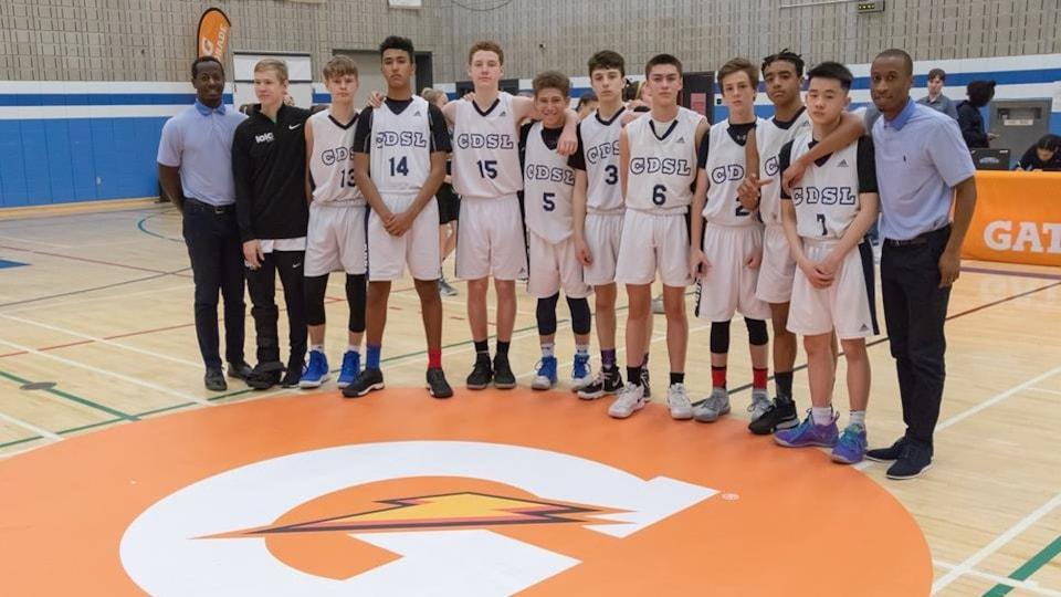 Des joueurs de basketball posent ensemble sur un terrain.
