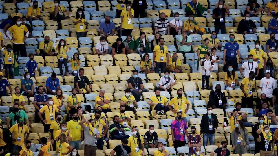 Unos pocos asientos vacíos separan a los aficionados, que en su mayoría visten de amarillo.