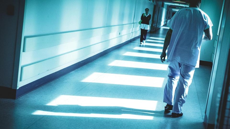 Deux personnes se croisent en marchant dans un couloir d'hôpital.