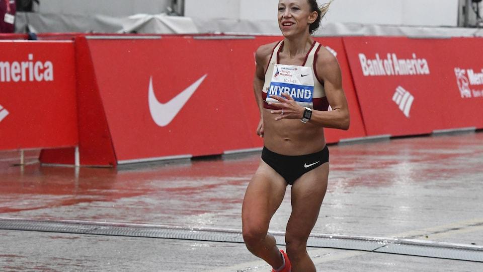 L'athlète est en pleine poussée, chaussures de couleur orange fluo au pied.