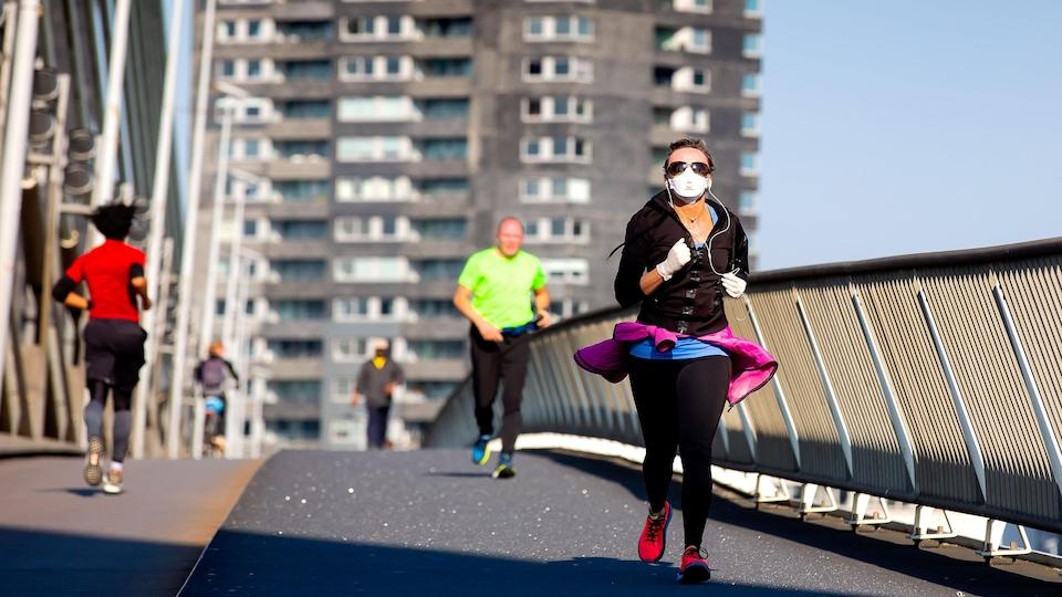Une femme fait de la course à pied avec un masque et des gants.