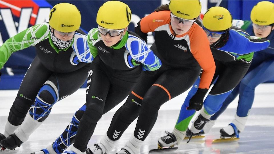 Des filles patinent sur la glace l'une derrière l'autre.