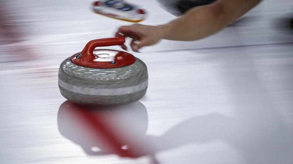 Une pierre de curling est lancée sur la glace.