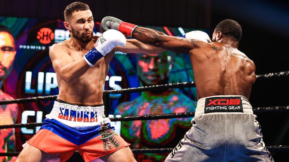 Un boxeur reçoit un coup de poing d'un autre combattant qui lui en envoie un en pleine figure en même temps.