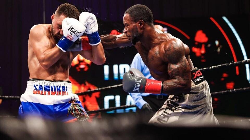 Un boxeur donne un coup sur le visage de son adversaire qui encaisse. Ça semble lui faire mal.