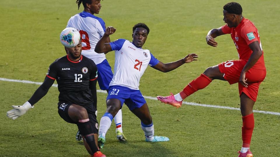 Le gardien haïtien Josué Duverger et son coéquipier Bryan Alceus plongent pour bloquer un tir du Canadien.