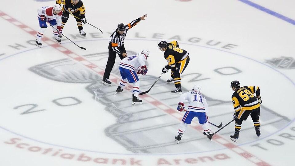Les joueurs attendent la mise au jeu au centre de la patinoire.