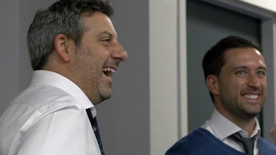 Deux hommes regardent devant eux avec le sourire.