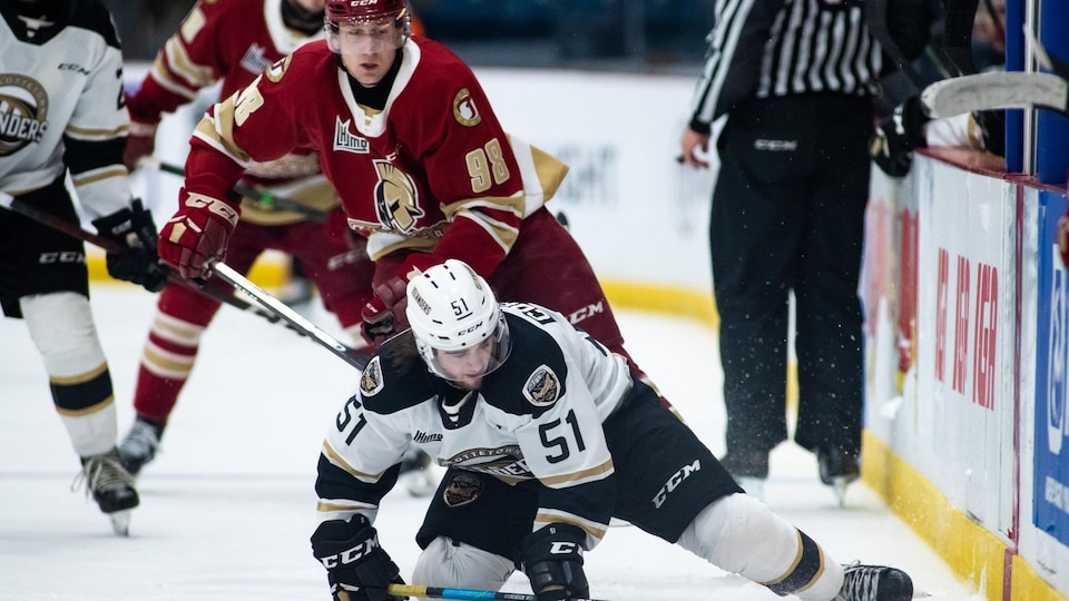 Deux joueurs de hockey. L'un est debout l'autre à genoux.
