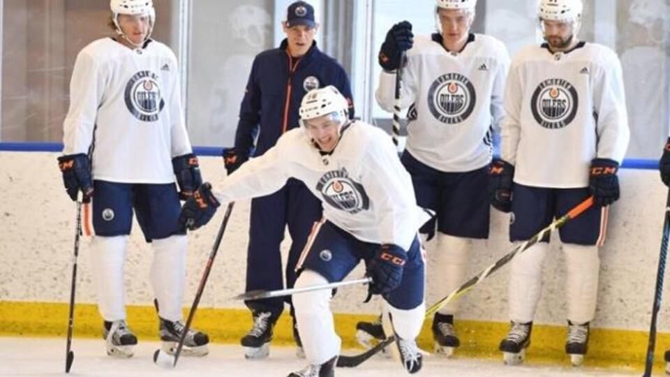 Un entraîneur dirige un groupe de joueurs de hockey.