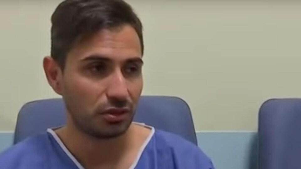 Un plan large de Davide Capello dans sa jaquette d'hôpital