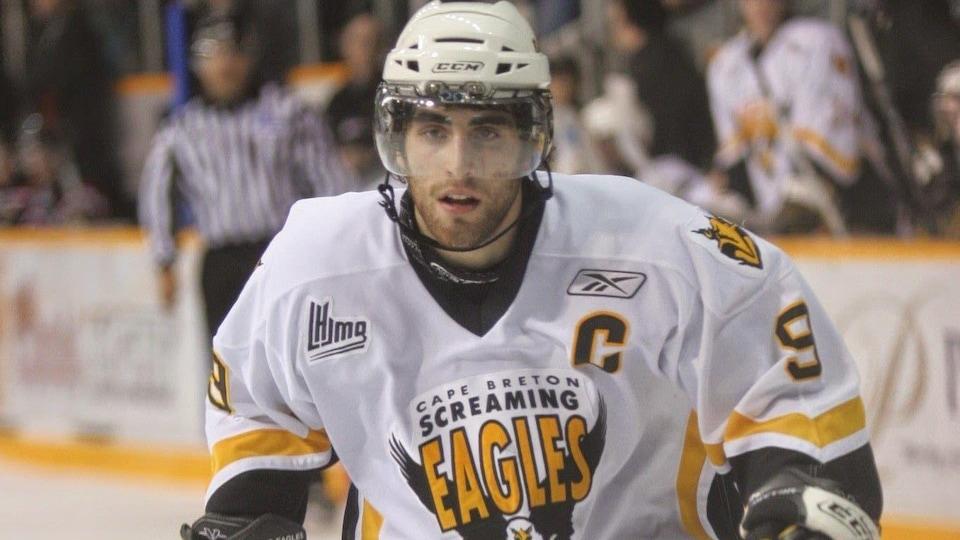 Joueur de hockey dbout avec son équipement. Il attend la rondelle.