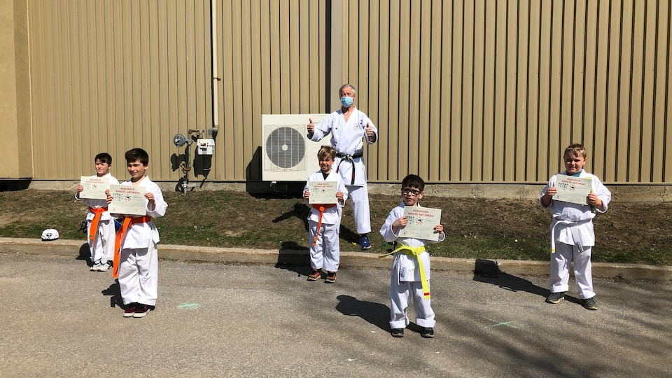 Un entraîneur les deux pouces dans les airs derrière cinq jeunes qui viennent de recevoir un diplôme.