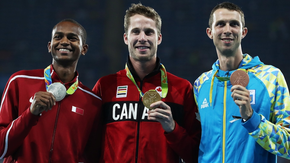 Il tient sa médaille d'or avec sa main gauche et il est entouré des médaillés d'argent et de bronze.