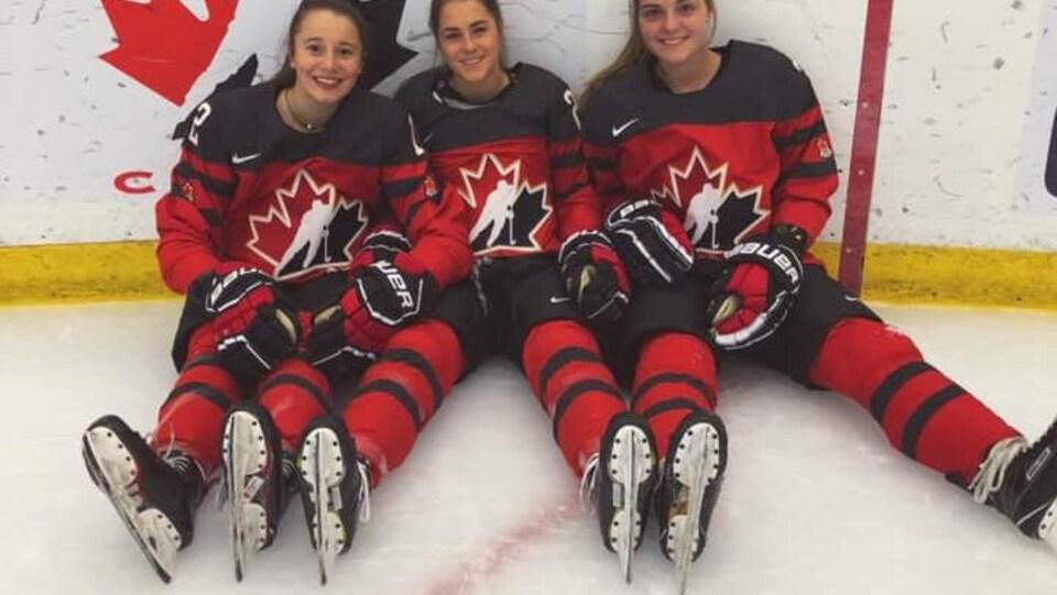 Dominique Cormier, de Sainte-Marie de Kent et ses coéquipières, assises sur la patinoire avec leur gilet de Hockey Canada