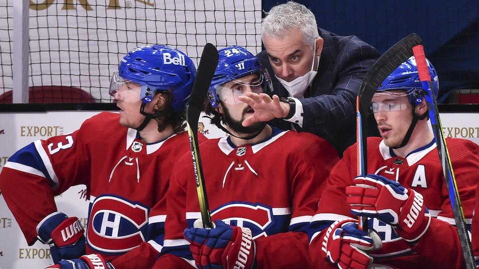 Un entraîneur de hockey derrière le banc avec trois joueurs.
