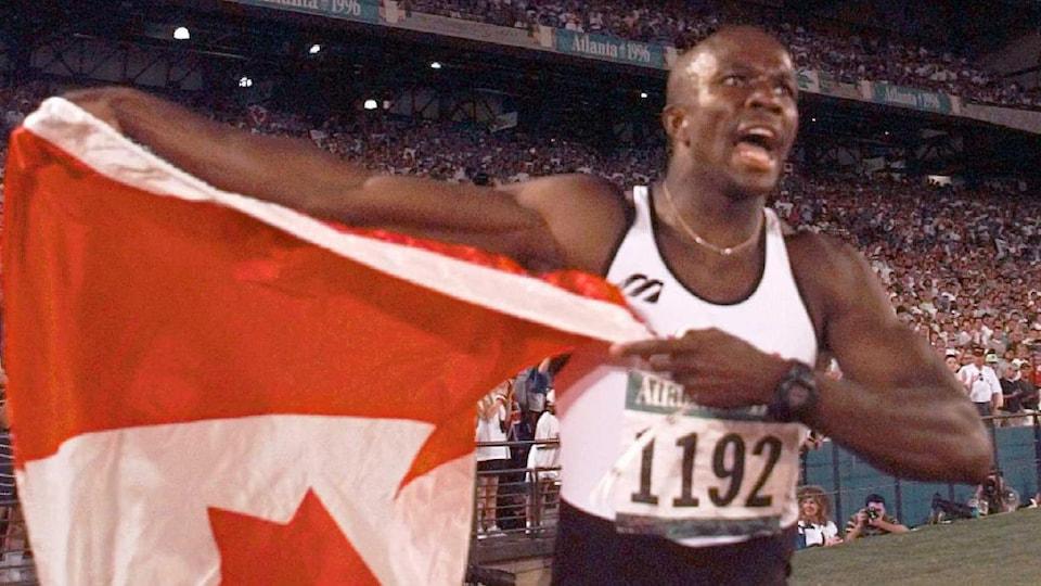 Il tient le drapeau canadien dans ses mains.