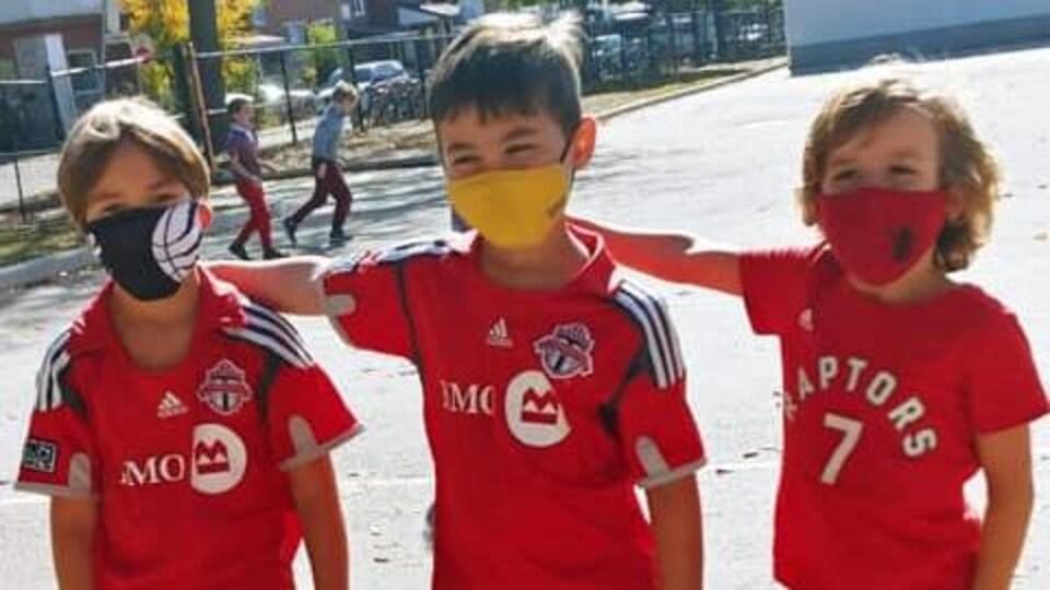Trois jeunes garçons portent des maillots rouges du Toronto FC.