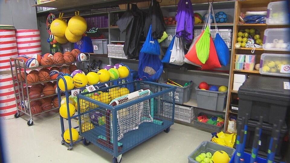 Des ballons et de l'équipement d'éducation physique dans l'entrepôt d'un gymnase.