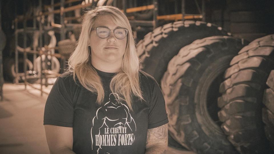 Une femme dans un hangar qui sert de gymnase, devant de gros pneus