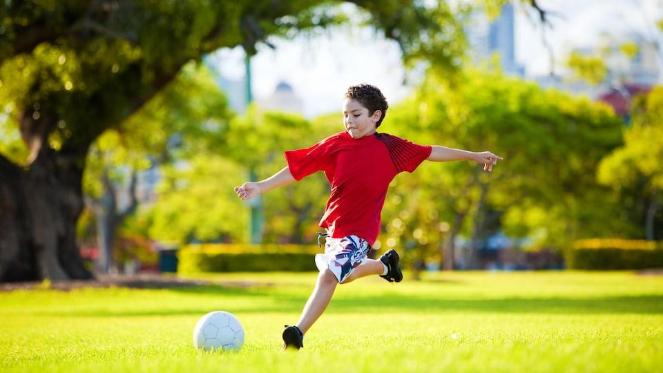 Un garçon joue au soccer dans un parc.