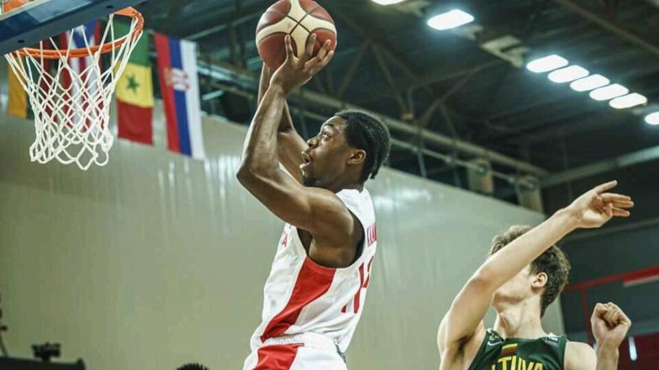 Un basketteur s'apprête à rentrer le ballon dans le panier sous les yeux d'un coéquipier et d'un adversaire.
