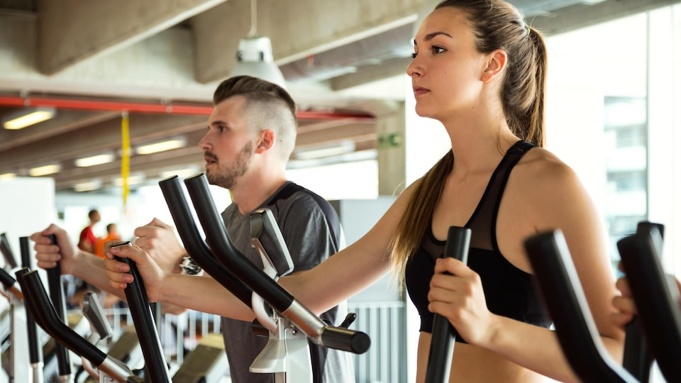 Un homme et une femme s'entraînent dans une salle de conditionnement physique.