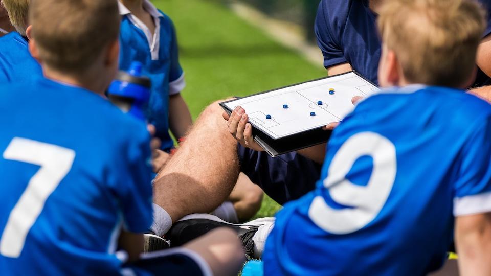 Des enfants sont accroupis et écoutent les conseils de leur entraîneur de soccer.