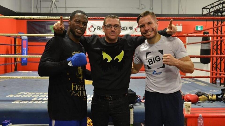 Un entraîneur pose devant un ring de boxe en compagnie de deux athlètes.