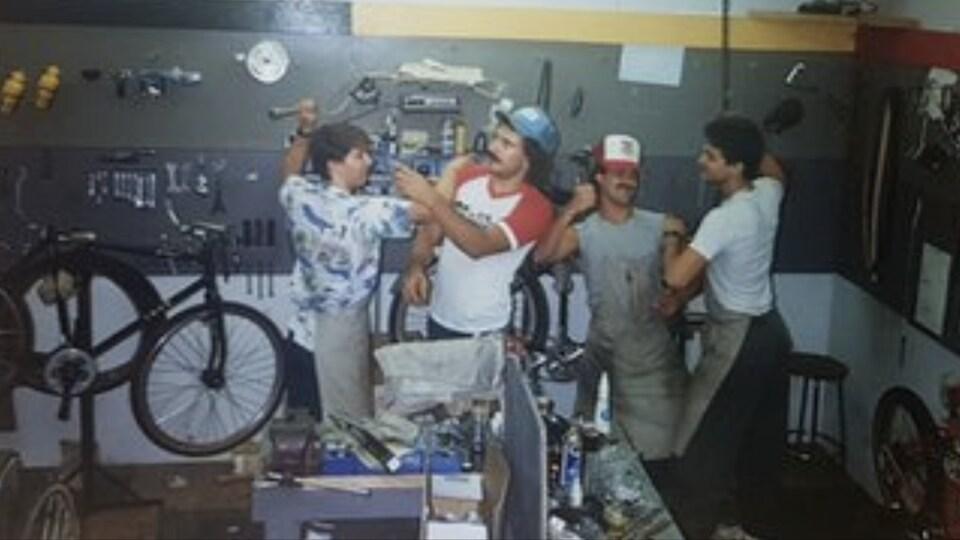 Un groupe de mécanicien de vélo s'amuse dans l'atelier.