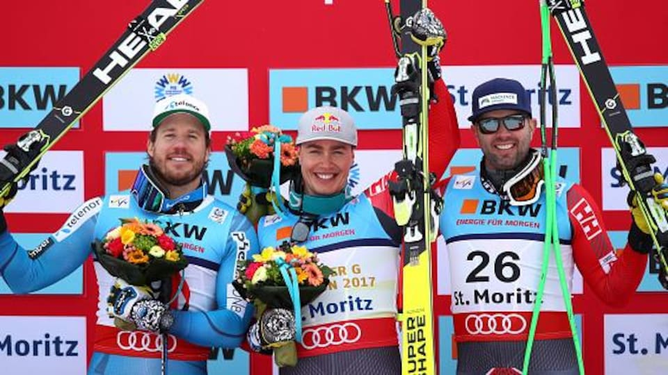 Erik Guay entouré de Kjetil Jansrud (gauche) et Manuel Osborne-Paradis sur le podium du super-G des mondiaux de Saint-Moritz.