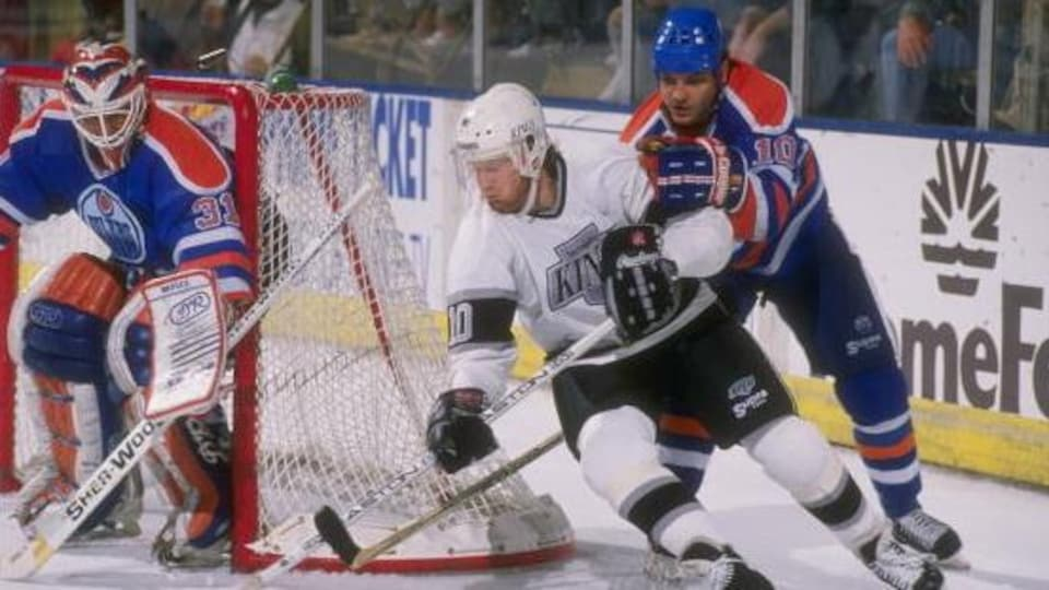 Esa Tikkanen (10), des Oilers d'Edmonton, tente de neutraliser Mike Allison, des Kings de Los Angeles.