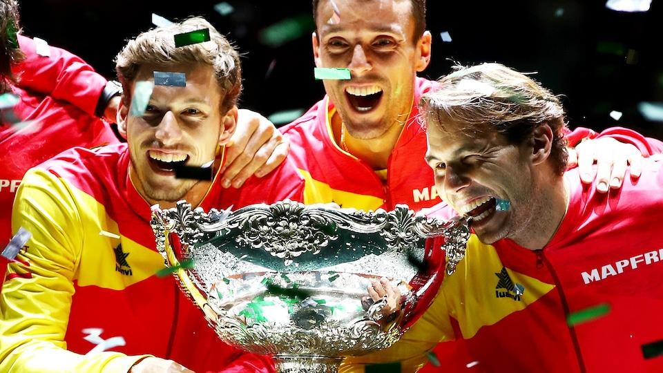 Avec ses coéquipiers et sous les confettis, Rafael Nadal mord le trophée pour les caméras.