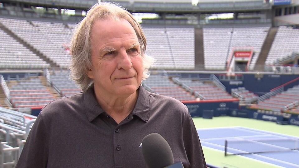 Il donne une entrevue près d'un terrain de tennis.
