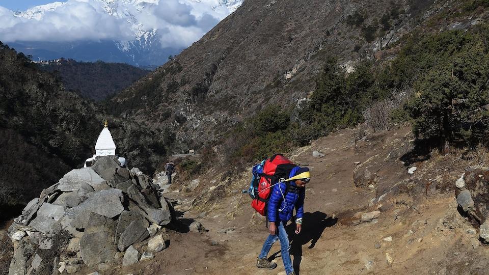 Un grimpeur apporte un sac vers un camp de base népalais, en route vers le sommet de l'Everest.