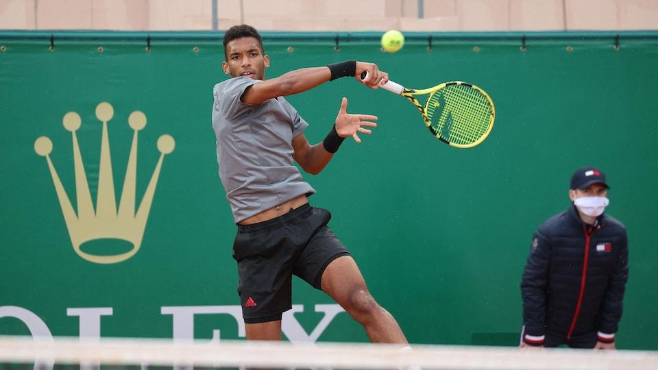 Un joueur de tennis, vêtu de gris et de noir, frappe une belle du coup droit en sautant dans les airs.